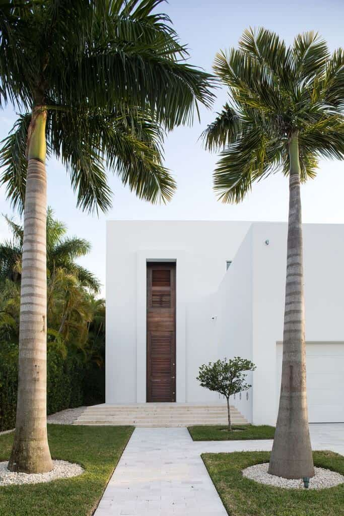 Tall palm trees surrounded by white pebbles accentuate the louvered front door against the white walls. It softens the sleek, minimalist design of the house.