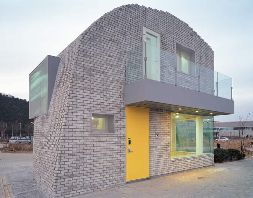 A yellow front door brings a pop of color in this concrete brick house with a unique design. It also creates a cheerful tone balancing the monotonous scheme of the house.