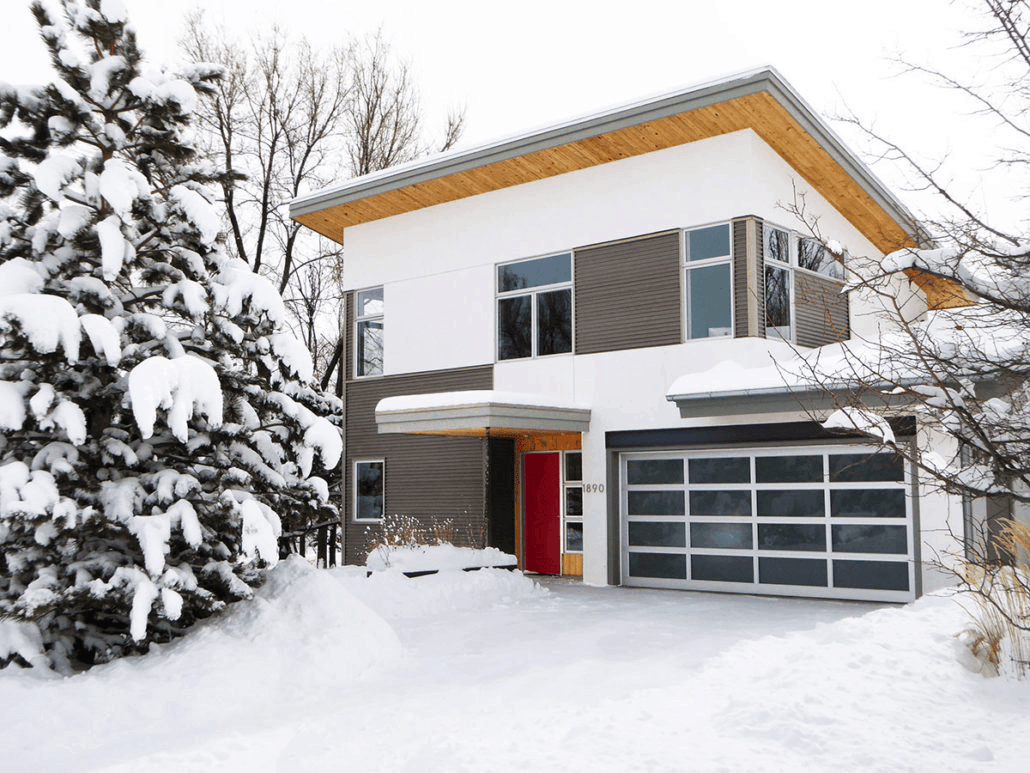 A red front door under a wood paneled ceiling stands out in this modern house that's covered in snow. Together with the neutral and wooden walls, they made an interesting exterior.