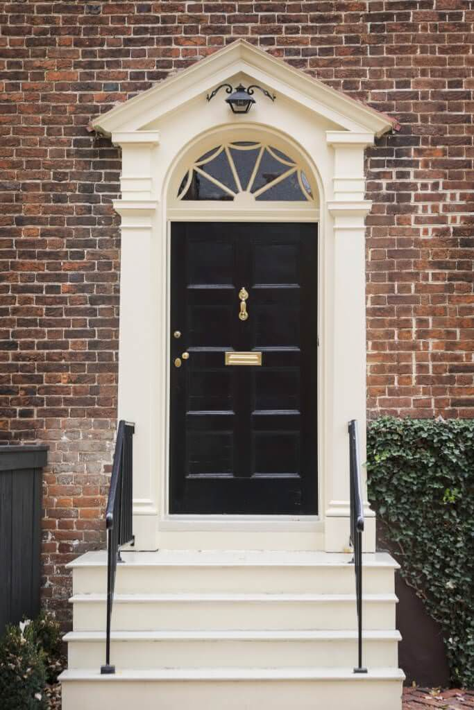A simple black door made elegant by a brass handle and plate. It is housed by a cream portico with a matching staircase contrasted by wrought iron railings.