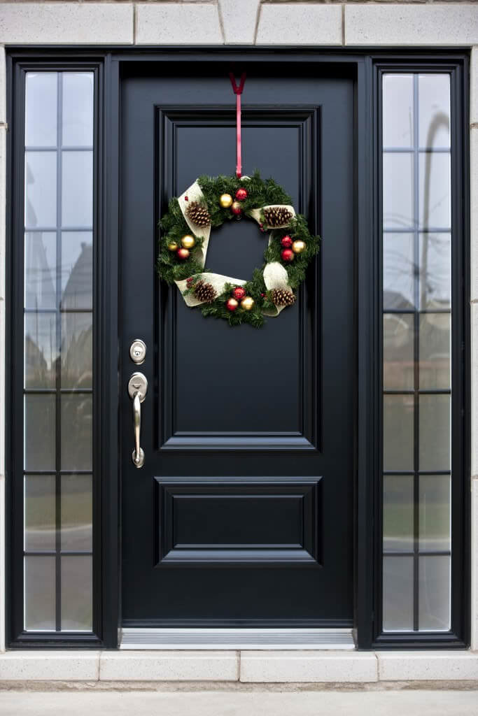 A sleek front door adorned by a lovely wreath. It is lined with glass insets framed in black aluminum.