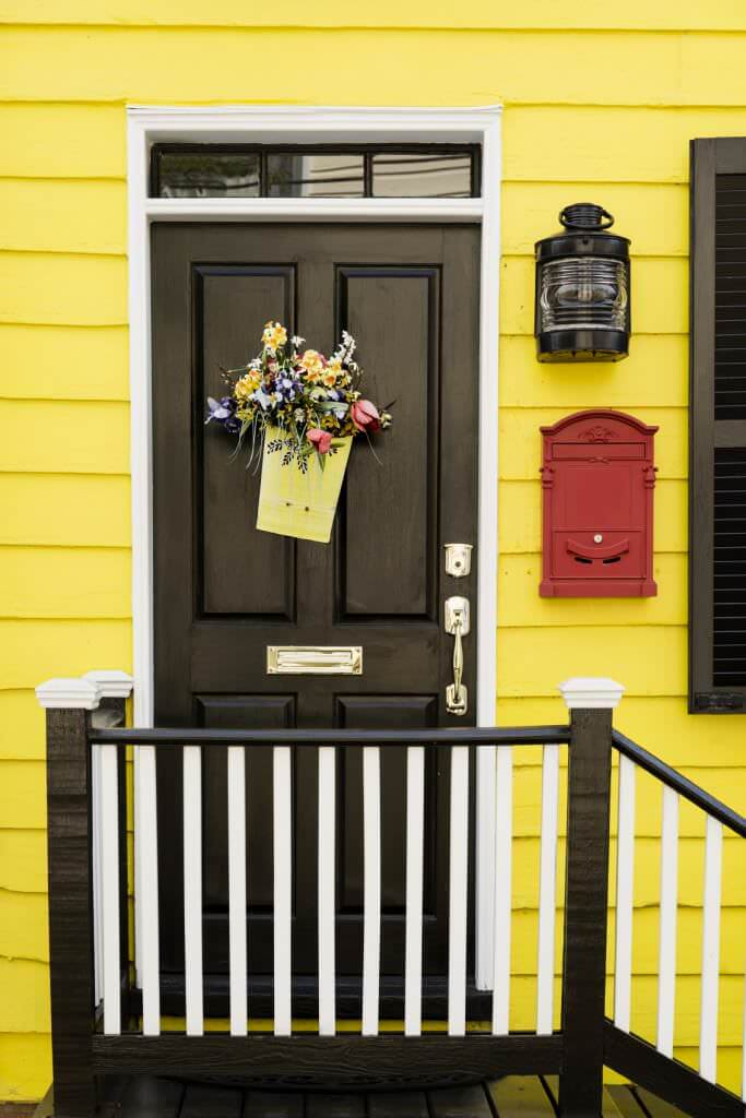 Bright yellow siding adds a cheerful tone to the black front door that's complemented by a sleek wall sconce and red mailbox. It is wrapped in a black and white staircase with a dark wood plank landing.