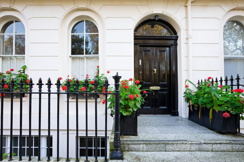 A black front door along with wrought iron fences add a striking contrast to the white walls that are fitted with arched windows. It is accented with gorgeous plants in black planters.