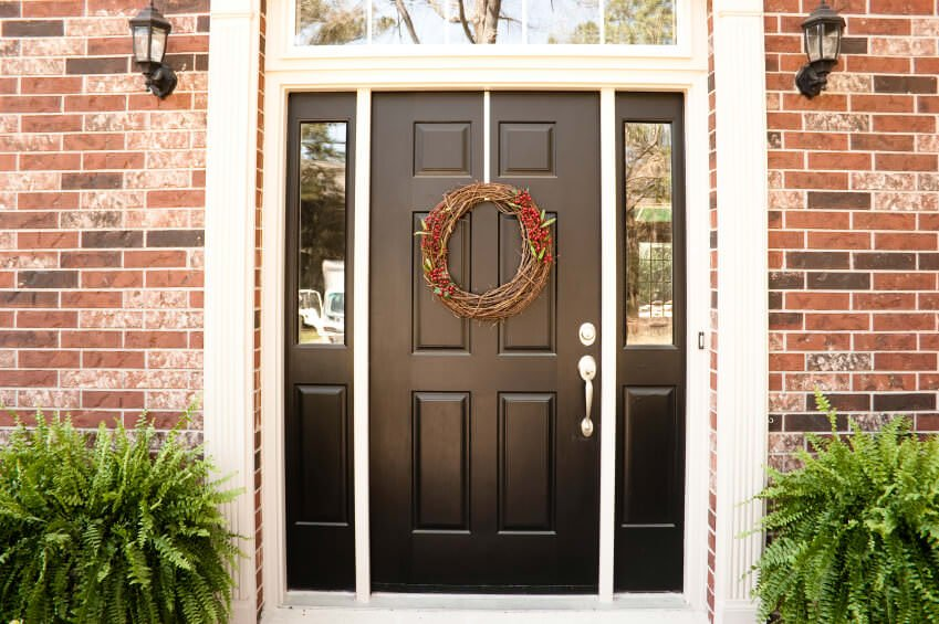 Adorned by a wicker wreath, this front door in dark wood is lined with white molding providing a sleek contrast to the entire look. It is flanked by traditional outdoor sconces and a pair of ferns which add life to the red brick walls.