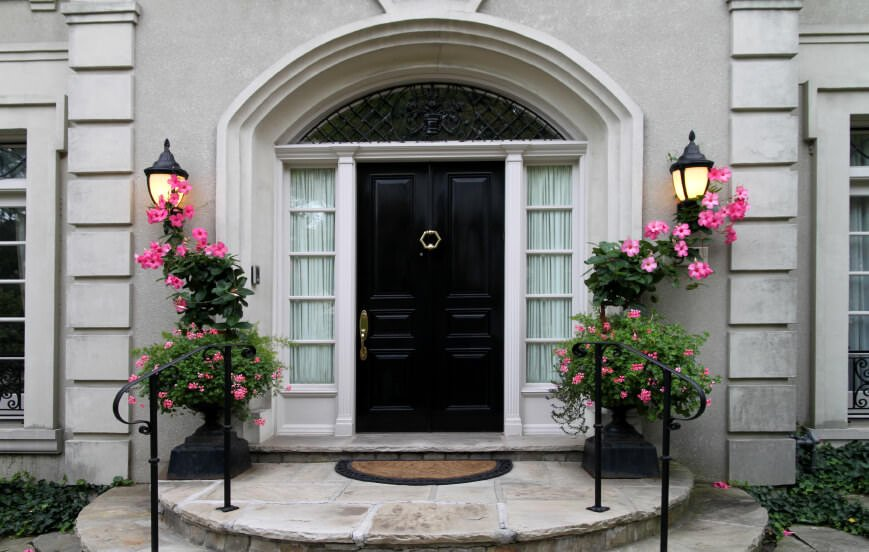 Lovely flowers accentuate the black front door with glass panels on the sides framed in a concrete arched trim. It is complemented by matching sconces and wrought iron railings that are fixed on a semi-circular staircase.
