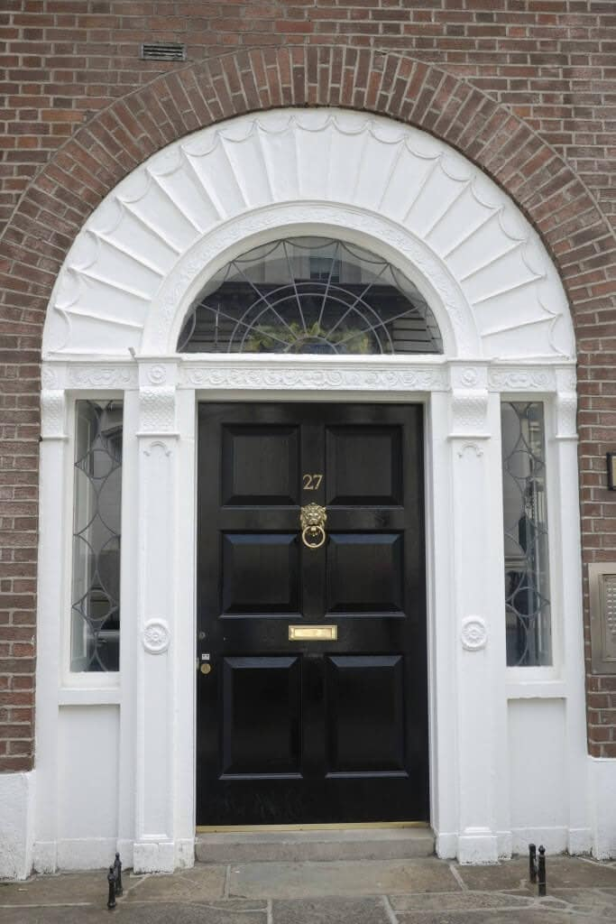 A black front door with brass hardware is surrounded by glass insets and white trims designed with intricate details making it stand out against the brick walls.