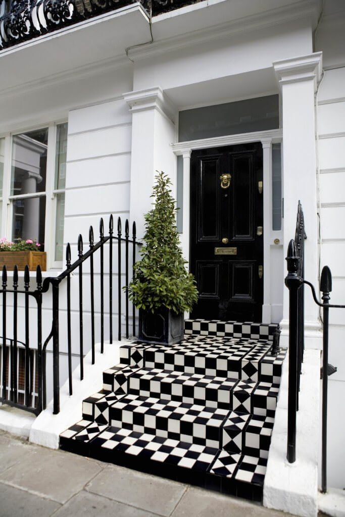Checkered staircase with wrought iron railings adds a striking accent to the front door that's adorned by antique brass knocker and plate. White walls and columns create a bright contrast highlighting the black door.