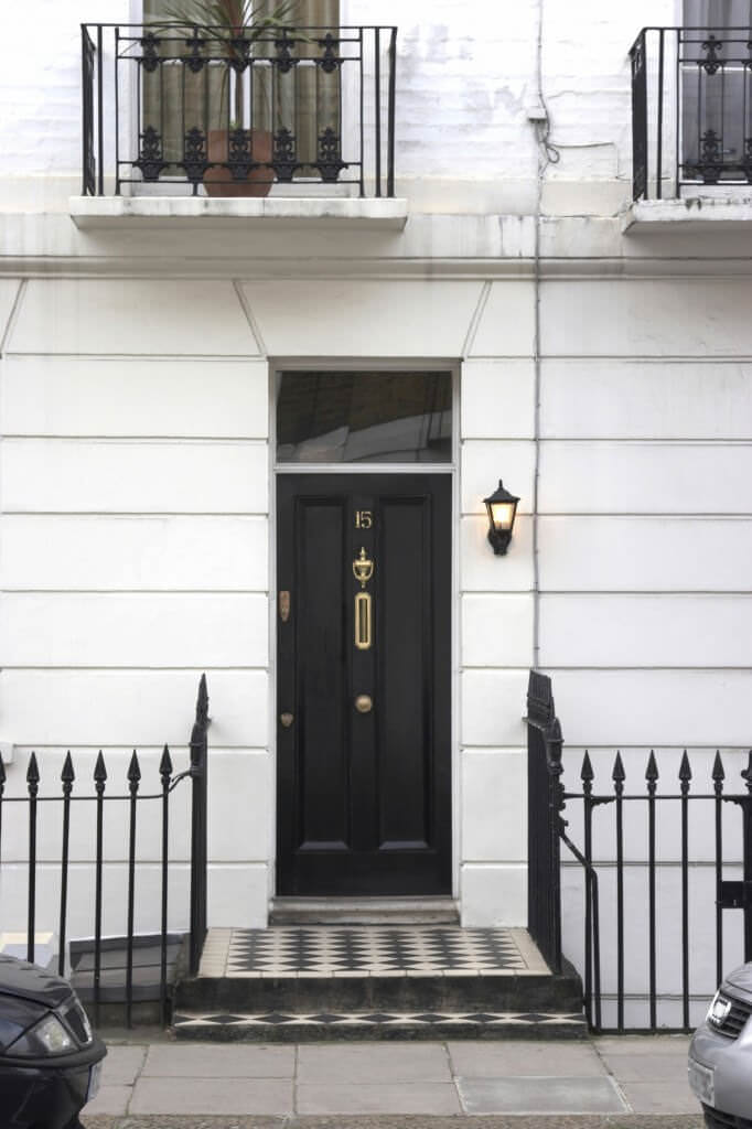 A slim front door provides a sleek contrast to the white walls that are mounted with a warm sconce. It is inlaid with a brass knocker and house number.