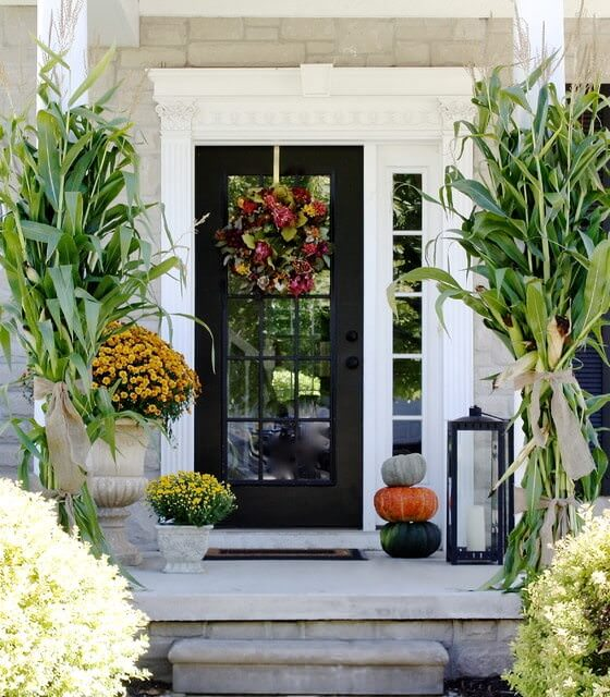 Various plants create a serene and fresh ambiance in this house with a mirrored front door framed in black aluminum. It is styled with greek columns along with decorative pumpkins and a large lamp over the concrete landing.