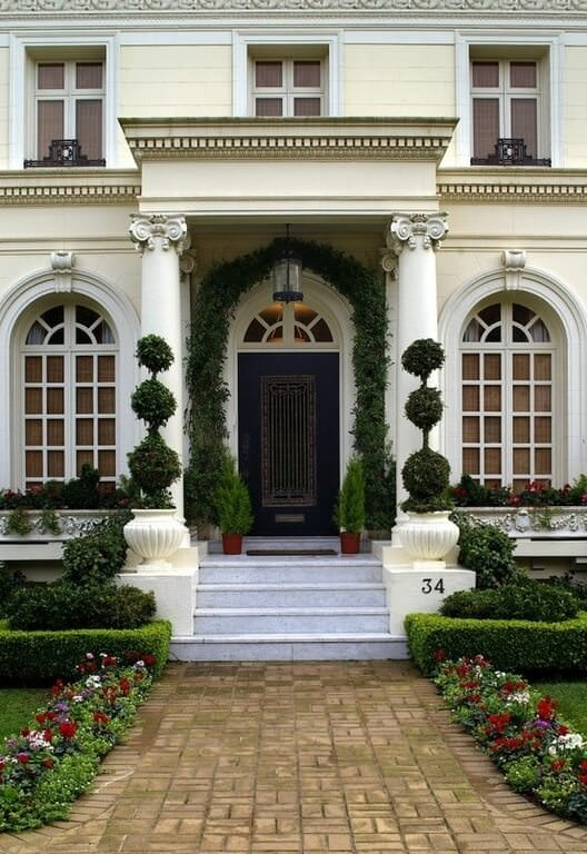 Arched windows flanked the black front door that's accented with a garland. It is accompanied by a tiled staircase with concrete planters on the sides filled with manicured <a class=
