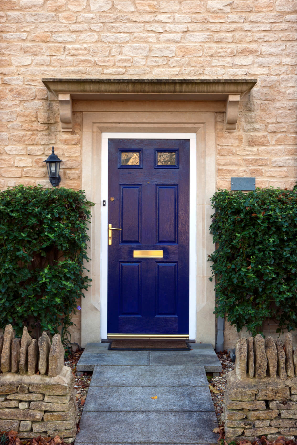 Almost similar to the above front door, this blue door with brass handle and plate is paired with a brown bordered rug and a traditional outdoor sconce mounted on the stone brick wall.