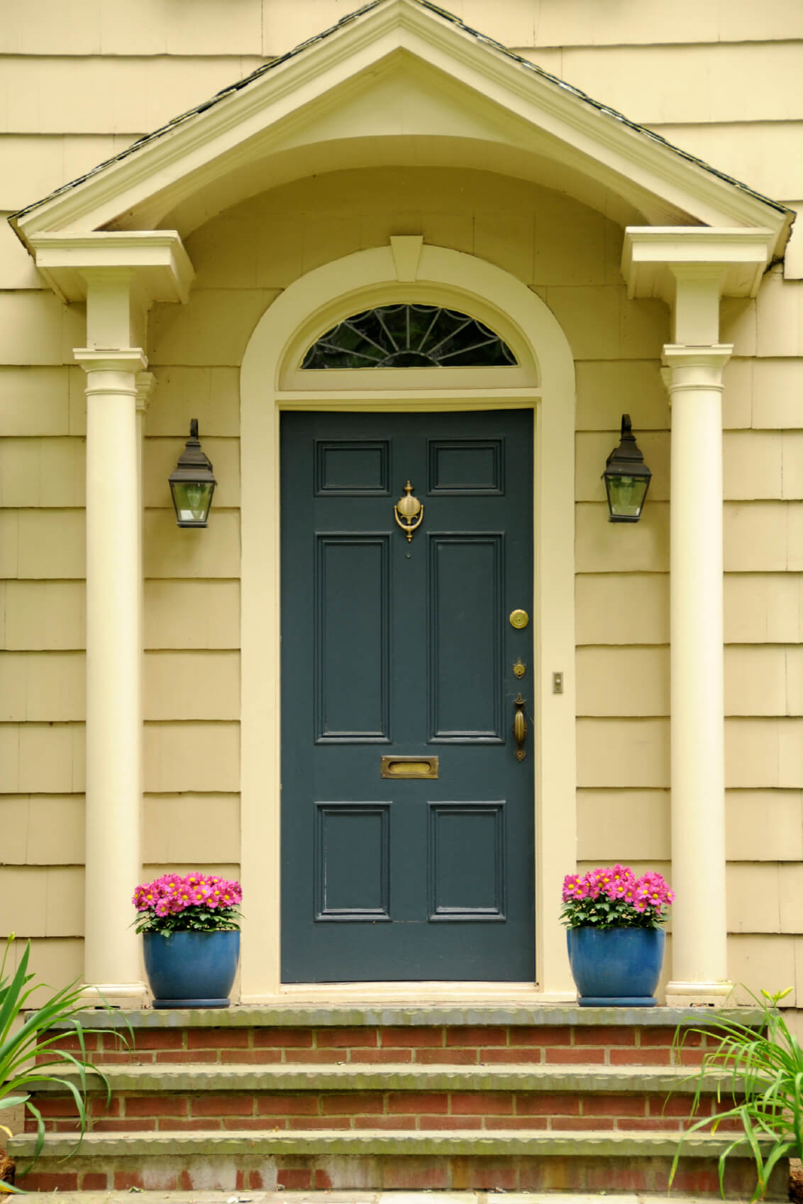 White columns and a pair of wall sconces along with lovely potted plants add a perfect symmetry to the blue front door that's fitted with brass hardware.