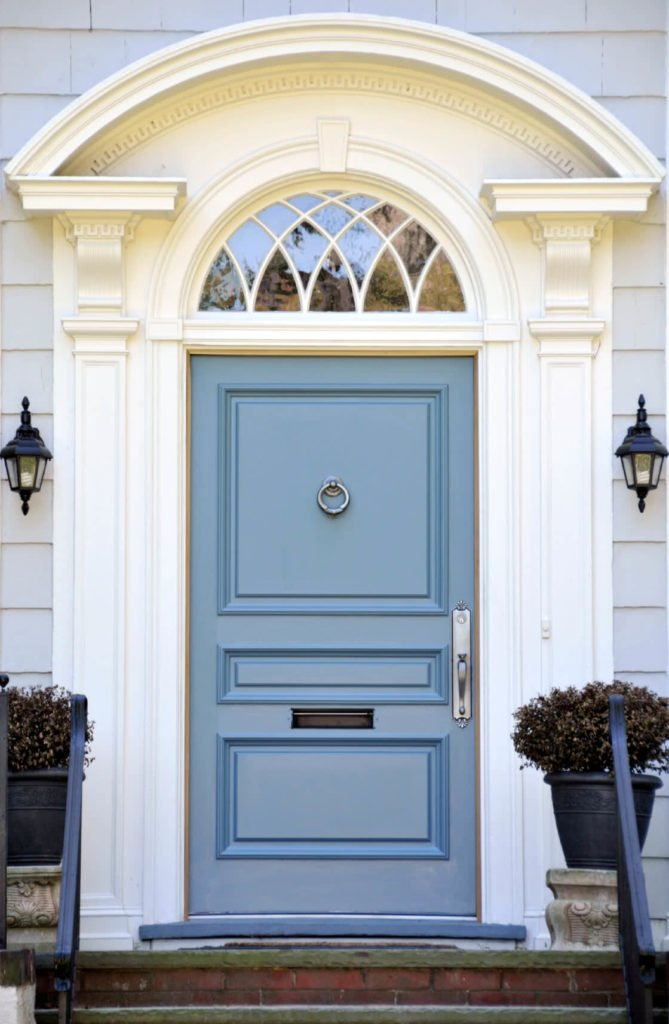 Traditional outdoor sconces illuminate the blue front door that's lined with fitted with chrome handle and a ring knocker. It is lined with arched trim and white columns.