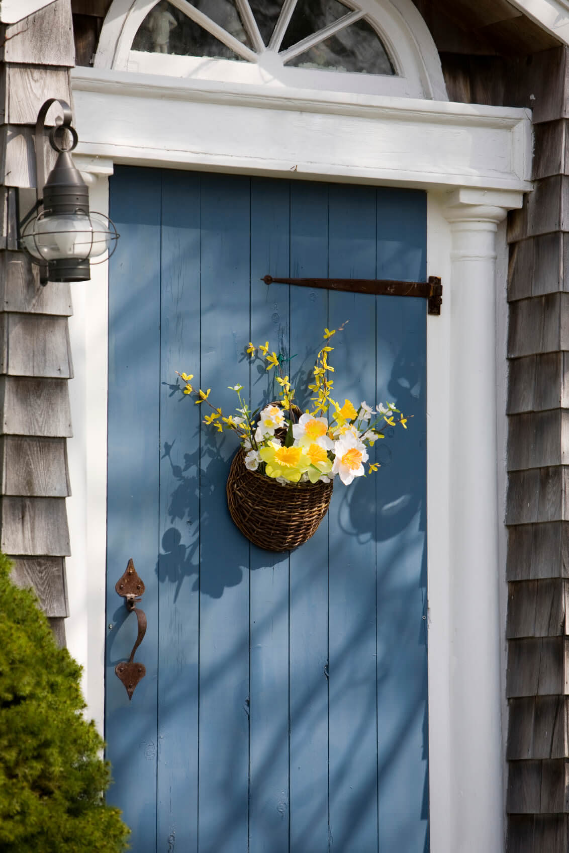 A simple blue front door adorned by a wicker plant holder stands out against the neutral sidings and white columns. It is paired with a metal sconce and a fresh plant on the side.
