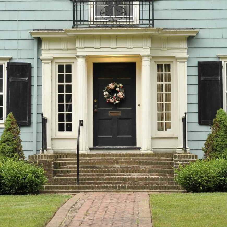 This house features a black front door that's accented with a gorgeous floral wreath. It is accompanied by white columns and a concrete staircase with straight paver under flanked by lush green lawns.