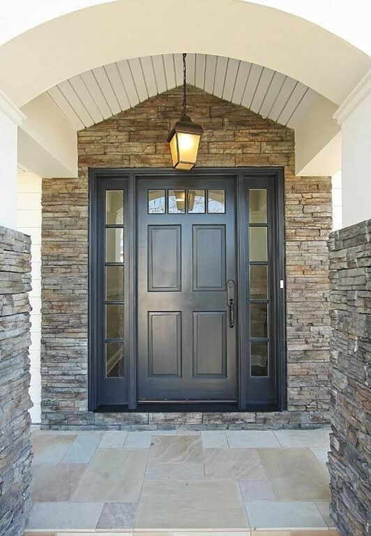Stone brick walls set a textured backdrop to the black door that's fitted with glass insets. It is illuminated by a warm lantern pendant that hung from the cathedral ceiling.