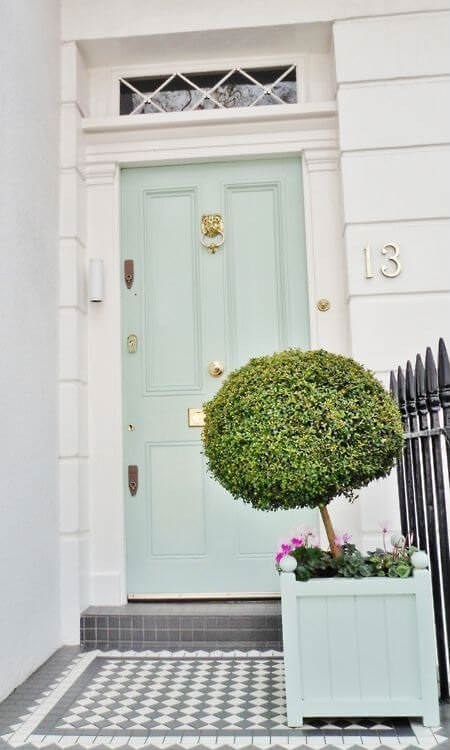 A mint green front door matches the planter box that's filled with a charming manicured shrub. It is guarded by a wrought iron fence over gray tiled flooring.