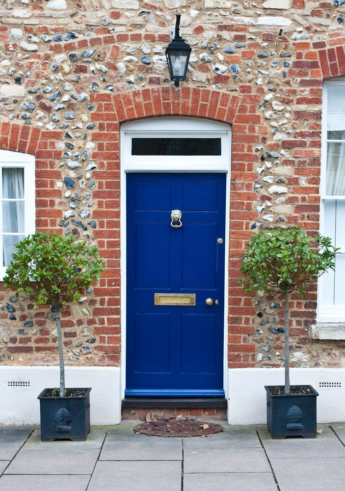Red brick walls incorporated with stone accents set a textured backdrop to the blue front door that's adorned by a lion knocker. It is complemented by a wrought iron lamp and tall potted plants over concrete tiled flooring.