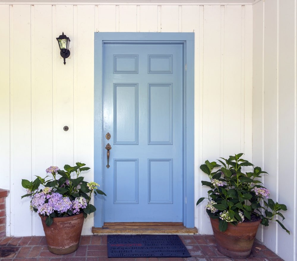 A sky blue front door with brass handle illuminated by a wall sconce mounted on the white beadboard. It is accompanied by potted plants and a deep blue rug over terracotta flooring.