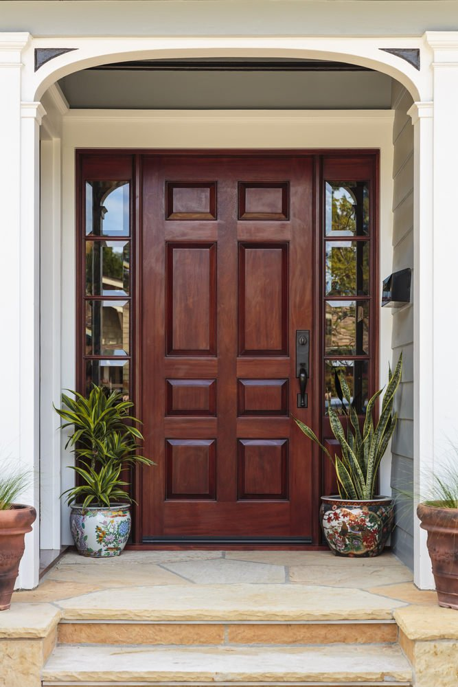 Flagstone entry stairs lead to this dark wood front door that's flanked by mirrored side panels. It is accented with a pair of hand painted ceramic pots.