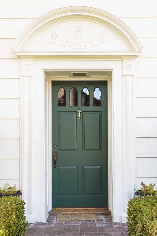 An emerald green door fitted with arched glass insets along with a bronze handle and a brass knocker. It is surrounded by white column moldings and an arched trim overhead that's designed with simple floral carvings.