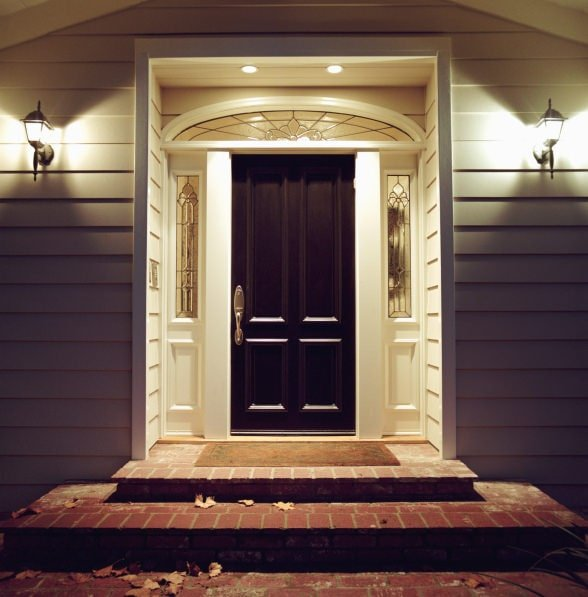 A view of the black front door at night with glass side panels and a small arched transom window illuminated by recessed lights. It is accompanied by a brown rug and traditional sconces mounted on the gray sidings.