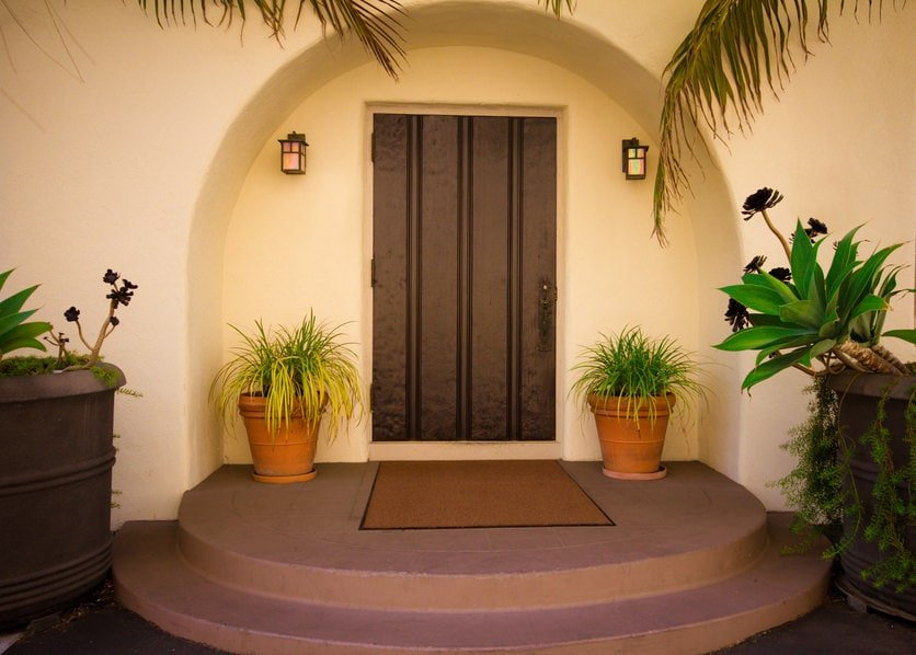 A simple wooden front door on an arched inset wall illuminated by outdoor sconces. It is complemented by green potted plants and a brown bordered rug over a concrete landing.