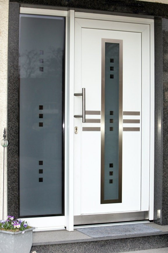 Contemporary white front door fitted with a sleek chrome handle that goes well with the frosted glass panel accented with silver trims.