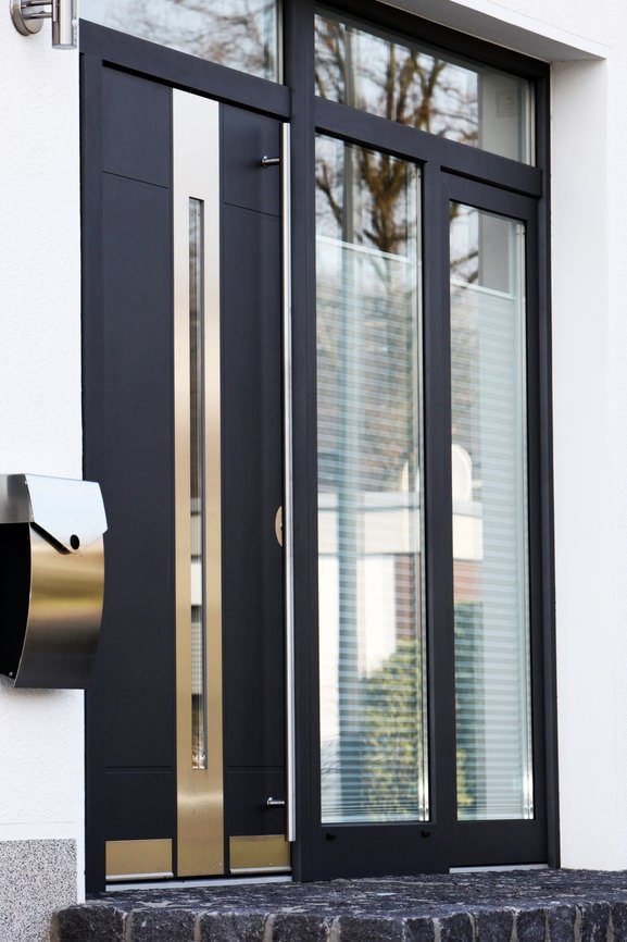 A black front door with mirrored panels enhancing its sleek look that goes well with the modern house. There's a brushed metal inset on the side matching with the chrome mailbox that's mounted on the white wall.