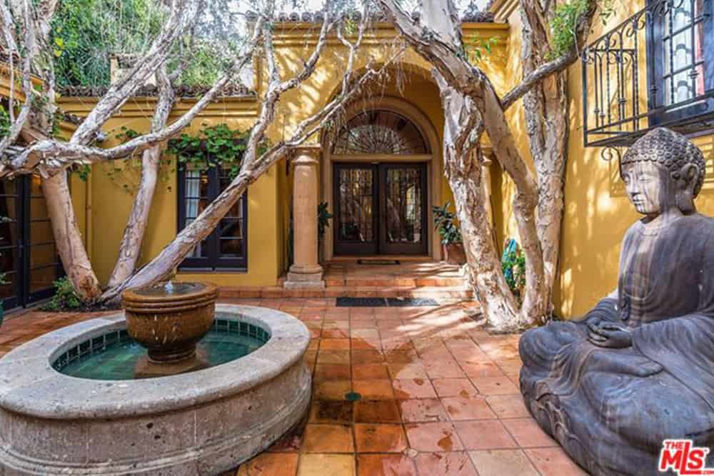 Spanish style house with an inviting courtyard featuring a large Buddha sculpture, fountain and enchanting trees along with a French front door that's lined with white columns.