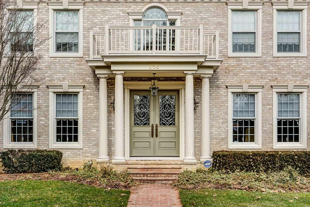 This brick house offers a gorgeous leaded glass double door surrounded by white columns. It is illuminated by a wrought iron pendant and matching sconces.