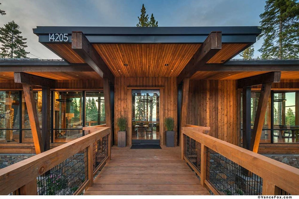 A glazed front door adds a modern touch to this all-wood house with a wood plank bridge framed in metal railings. It is complemented by sleek planters and a small black rug.