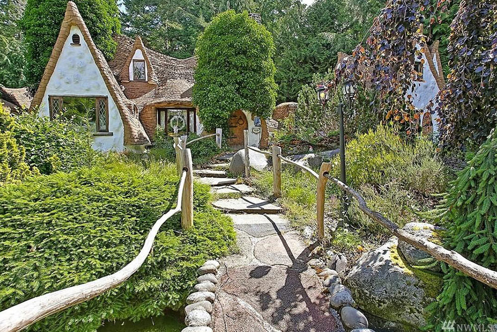 An enchanting house that perfectly blends in with its surroundings featuring a hobbit-like front door that's fitted with wrought iron hardware.
