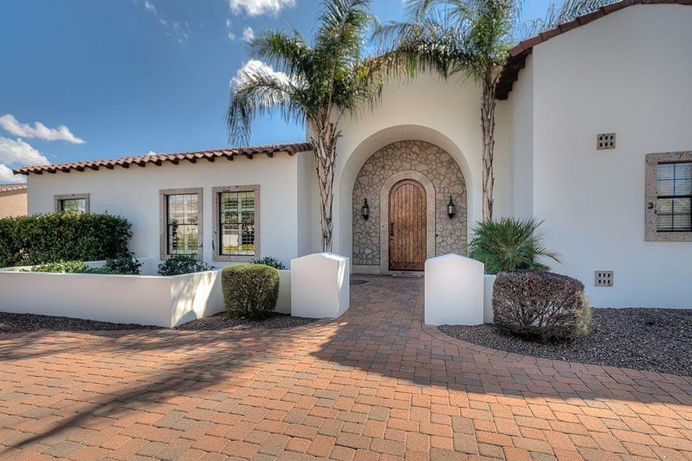 Stone arched border accentuates the wooden front door that's illuminated by sleek sconces. It is guarded by tall palm trees standing behind the concrete white fence.