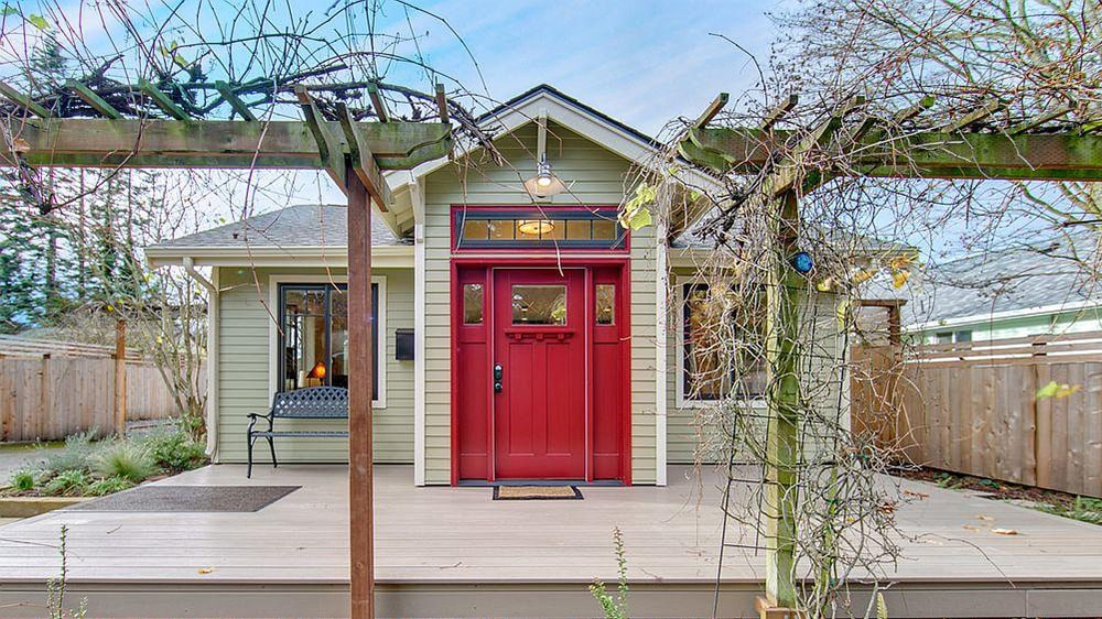 A bungalow house accented with a red front door that's fitted with small glass insets. It is complemented by a brown bordered rug over a light wood plank deck.