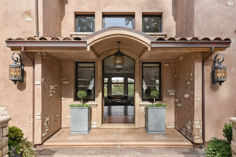 Concrete planters flanked the arched front door that's framed with a light wood surround. It is illuminated by a glass pendant light that hung from the barrel vaulted ceiling.