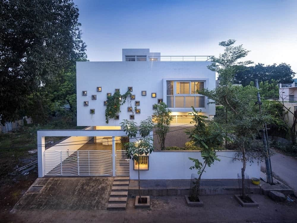 This is an aerial view of the front exterior of the house with white exterior walls complemented by the warm lighting as well as the creeping vines of the landscape that also has tall trees.