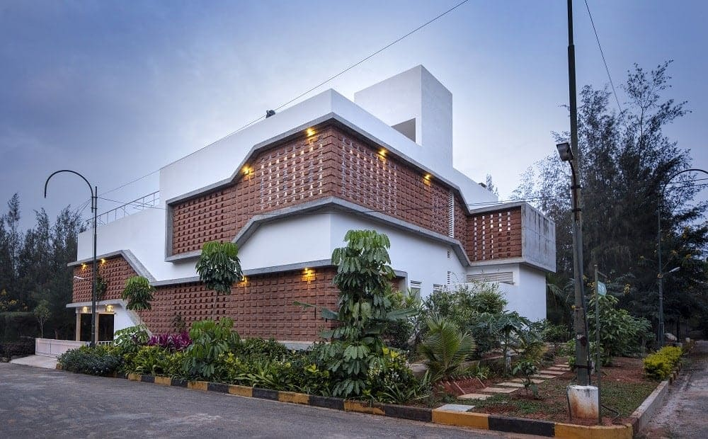 This is an exterior view of the house with large red brick walls that stand out against the white exterior walls and structures complemented by the surrounding lush landscaping of thick shrubs and walkways.