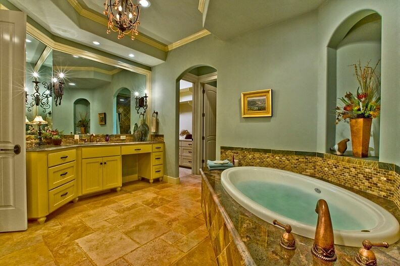 Traditional primary bathroom with limestone flooring and sage green walls accented with a brass framed artwork. It includes a beadboard vanity and a deep soaking tub under the arched inset wall niche that's filled with a copper vase.