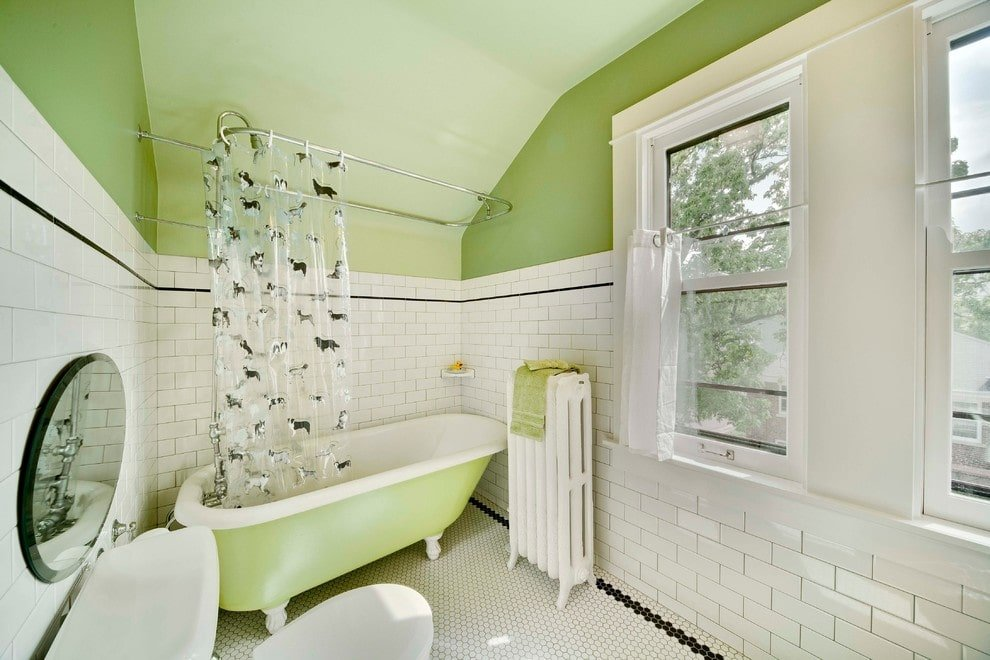 A round mirror hangs over the toilet sitting across the clawfoot tub in this primary bathroom with hex tile flooring and green walls dominated by white subway tiles.