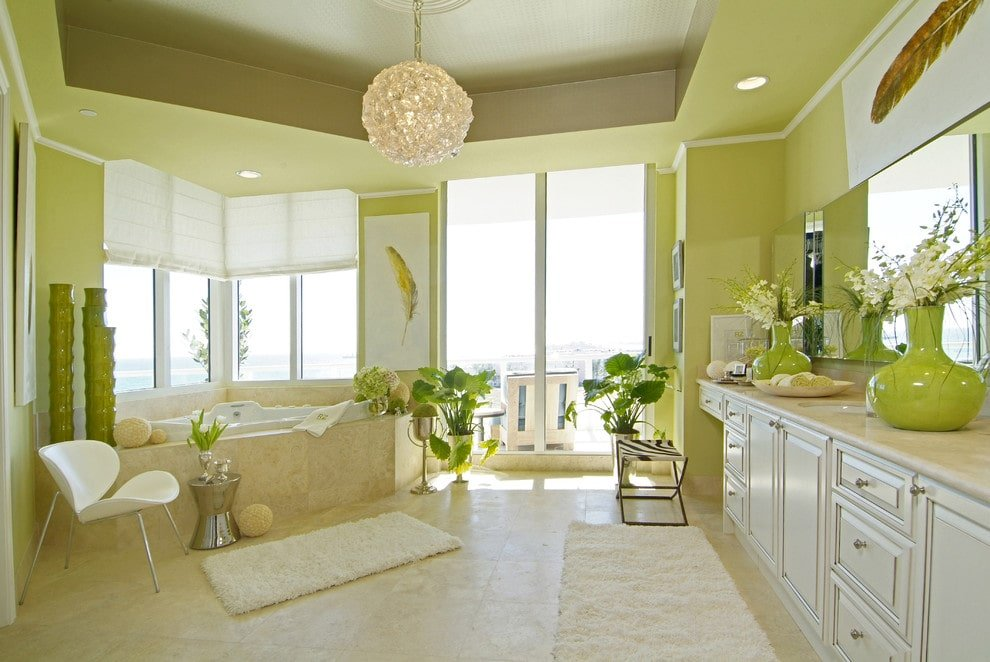 A contemporary white chair sits next to the corner tub facing the large vanity that's topped with apple green vases. It is illuminated by recessed lights and a round crystal pendant that hung from the tray ceiling.