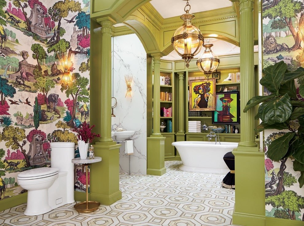 This primary bathroom showcases a combination of olive green walls and wildlife wallpaper providing a gorgeous backdrop to the potted plant and toilet. It has a wash area and a freestanding tub against the built-in shelving lighted by spherical glass pendants.