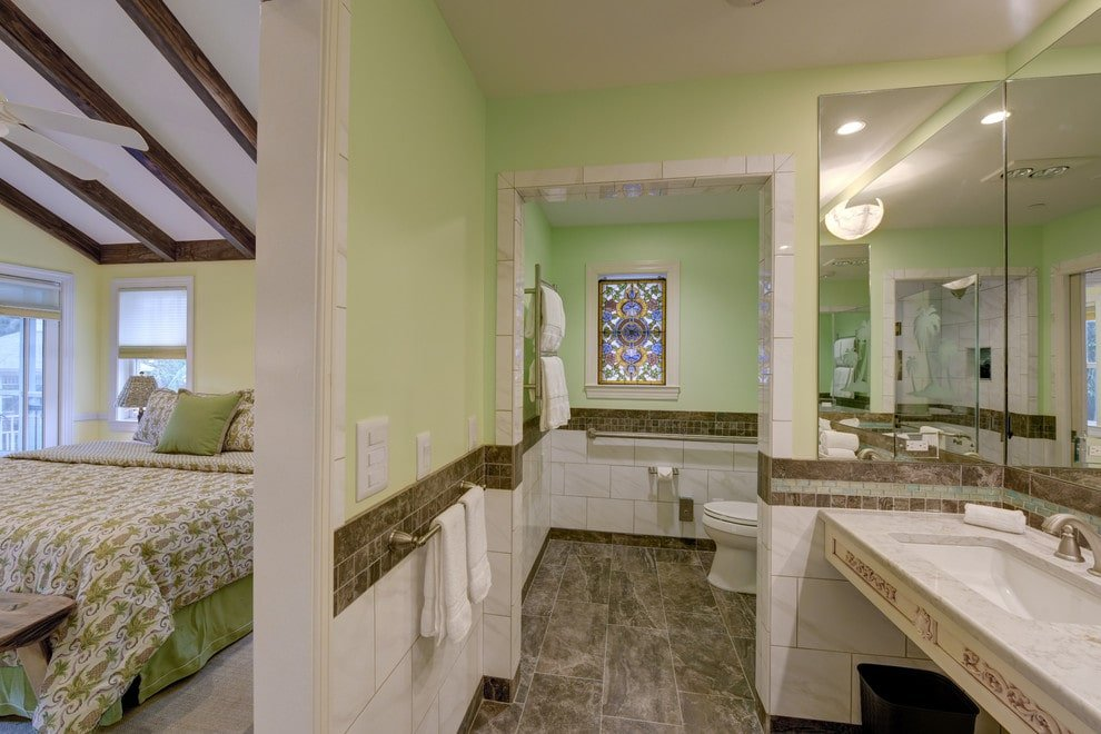 A gorgeous glass stained window stands out against the light green walls that are accented with brown border tiles matching with the marble flooring. This room boasts a toilet area and a sleek washstand paired with frameless mirrors.
