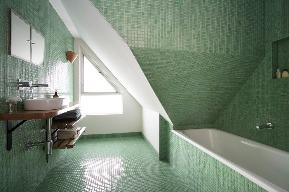 Clad in green mosaic tiles, this master bathroom offers a drop-in bathtub and a floating washstand with a vessel sink and wood plank shelves underneath. It is paired with an inset medicine cabinet enclosed in double mirrored doors.