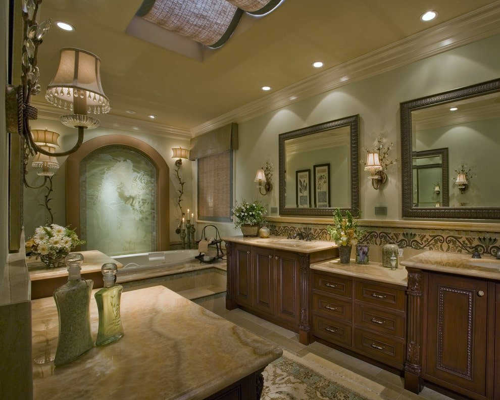 An enchanting arched mural sets a classy backdrop to the deep soaking tub facing the dark wood vanities that are paired with framed mirrors. It is illuminated by charming sconces and recessed ceiling lights.