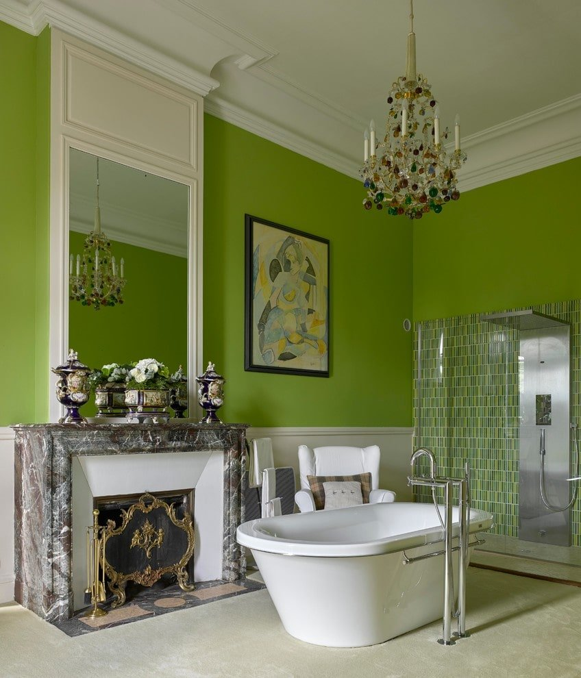 A colorful chandelier illuminates this primary bathroom boasting a walk-in shower and a freestanding tub with a white wingback chair on the side along with a marble fireplace that's enclosed in an elegant gold screen.