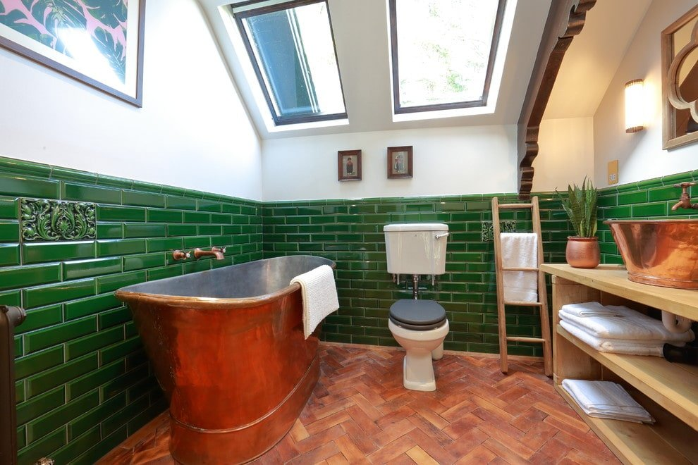 A copper freestanding tub matches the vessel sink that sits on a light wood shelving against the green subway tiles. This room features herringbone wood flooring and vaulted ceiling fitted with skylight windows.
