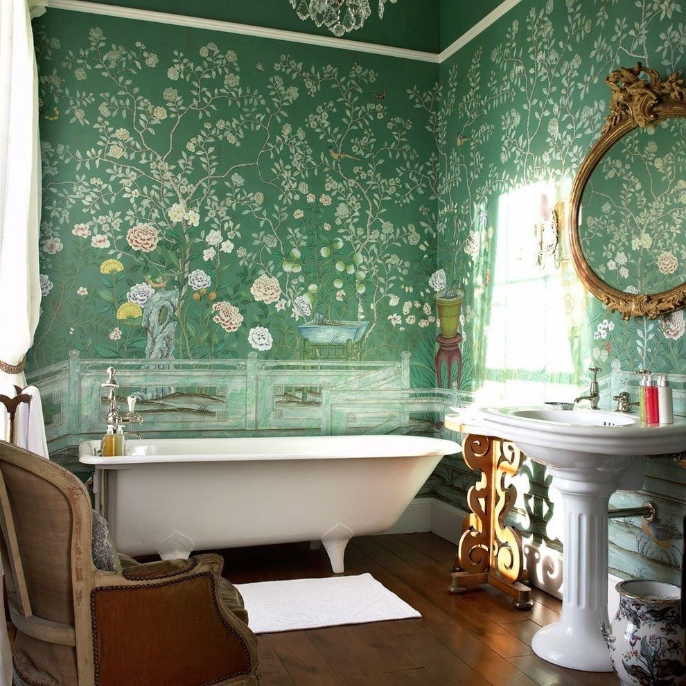 Clad in green floral wallpaper, this primary bathroom boasts a freestanding tub and a pedestal sink under an ornate round mirror. It is accompanied by a ceramic vase and a wooden armchair over wide plank flooring.