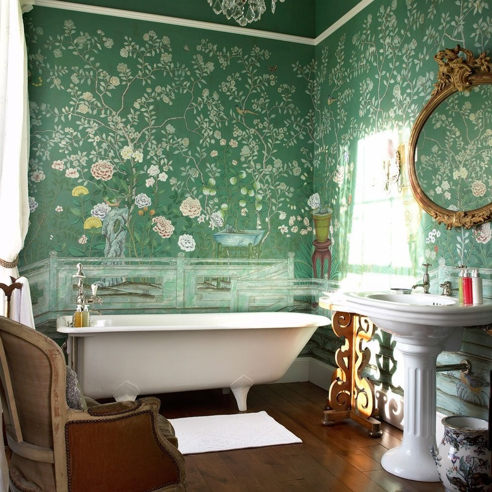 Clad in green floral wallpaper, this master bathroom boasts a freestanding tub and a pedestal sink under an ornate round mirror. It is accompanied by a ceramic vase and a wooden armchair over wide plank flooring.