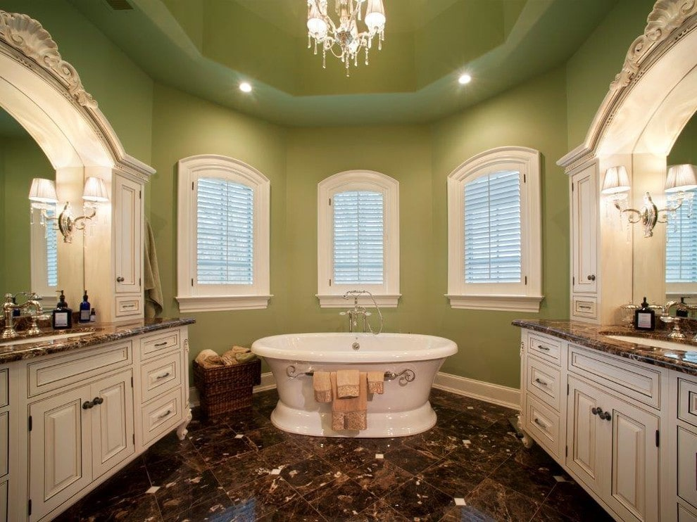 A crystal chandelier that hung from the tray ceiling illuminates the freestanding tub by the arched windows covered with white shutters. It is flanked by white vanities with granite countertops matching with the tiled flooring.